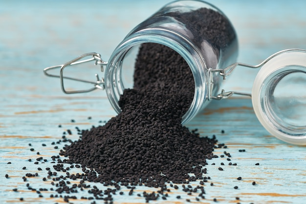 Семена черного тмина наливают из стеклянной банки на синий деревянный стол