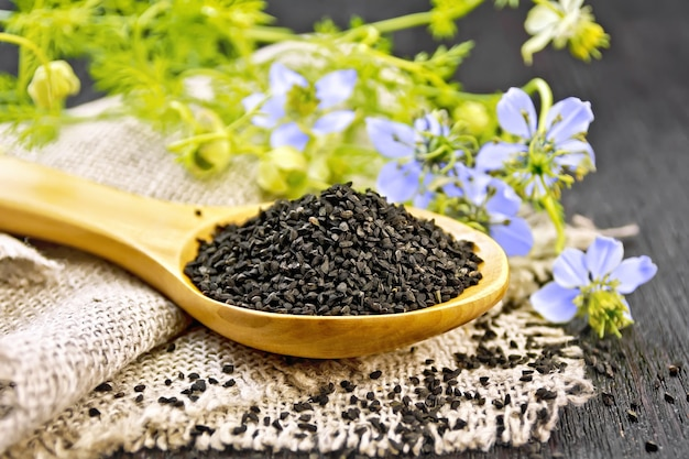 Семена черного тмина в ложке на мешковине, веточки калинги с синими цветами и зелеными листьями на фоне деревянной доски