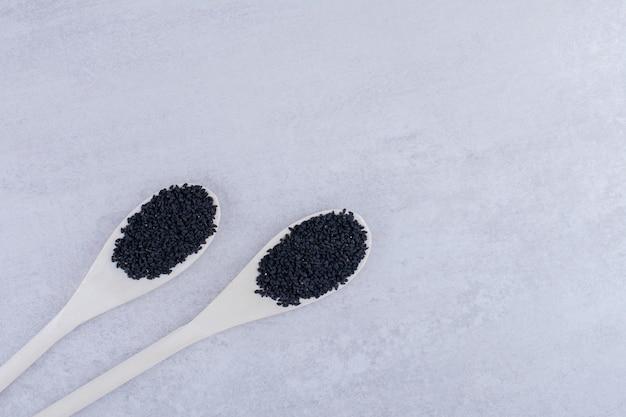 나무로되는 숟가락에 검은 커민 씨앗. 고품질 사진