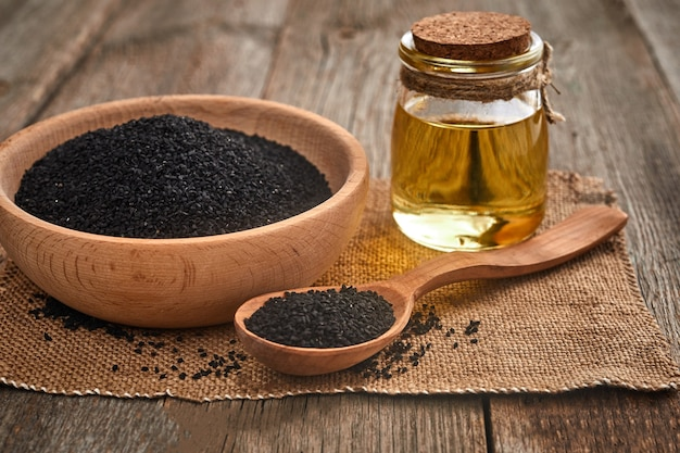 Black cumin seeds and a wooden spoon, bowl with bottle of oil on a wooden table.