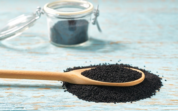 Black cumin in a wooden spoon and open glass jar on a blue wooden background, with copy space.
