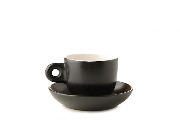 黒のカップとソーサーを白で隔離
