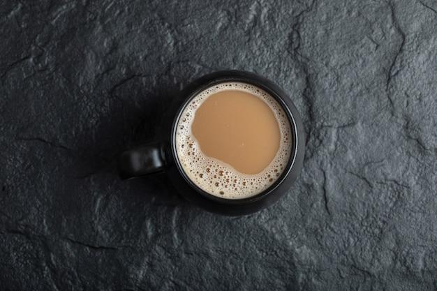 Una tazza di caffè nera su fondo nero.