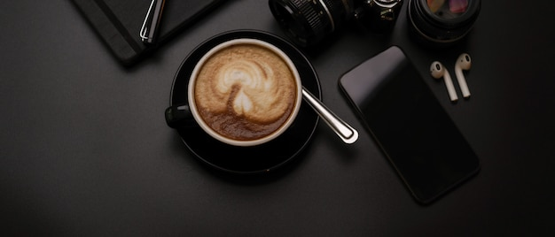Black cup of coffee on dark office desk with camera, smartphone, schedule book and wireless earphone