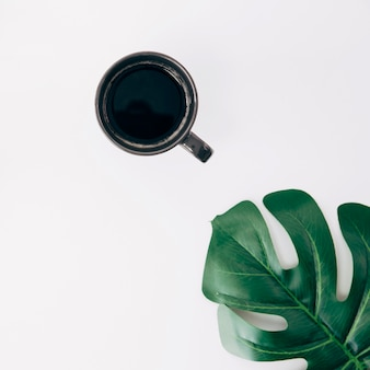 Black cup of coffee and green monstera leaf on white background