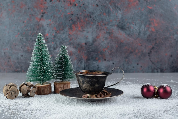 Black cup of coffee with christmas decorations on coconut powder on marble surface