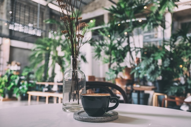 A black cup of hot coffee on table in cafe