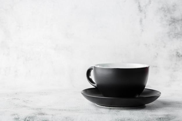 Черная чашка изолированная на белой мраморной предпосылке. горизонтальное фото. магазин посуды. магазин посуды. реклама для магазина посуды.