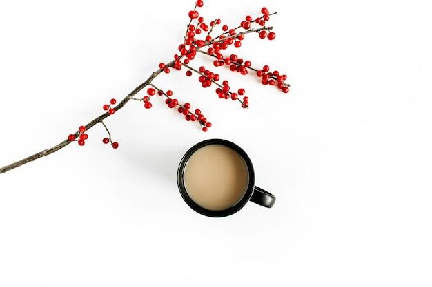 白いテーブルの上の赤いベリーの枝とコーヒーの黒いカップ。フラットレイ、上面図。