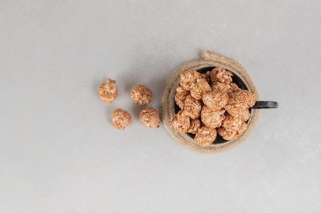 Tazza nera traboccante di popcorn canditi marroni sul tavolo di marmo.