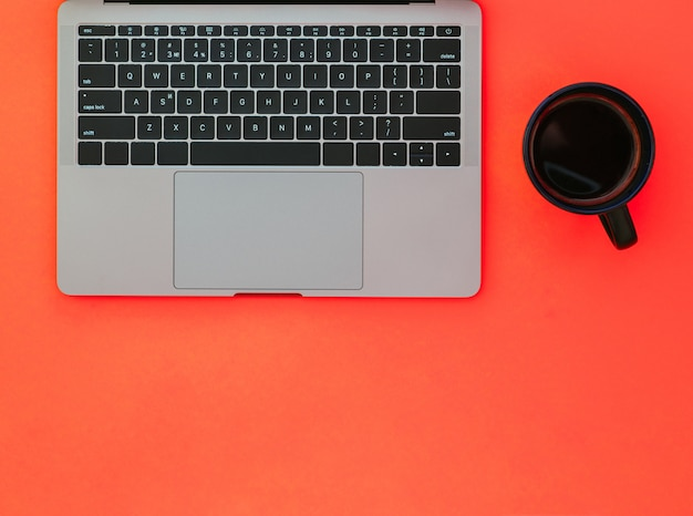 커피와 빨간 표면에 회색 노트북 블랙 컵