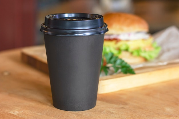 Black cup with coffee to go on background with burger, mock up