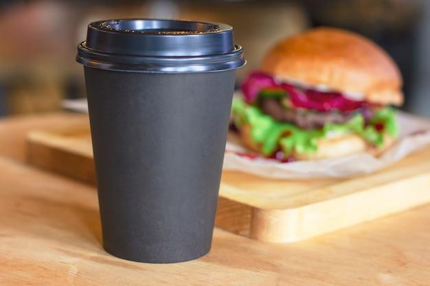 Черная чашка с кофе, чтобы пойти на фоне с гамбургером, макет