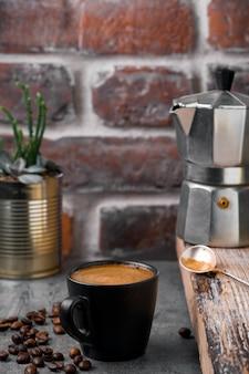 Черная чашка с кофе эспрессо, кофейником и кофейными зернами на сером каменном столе.