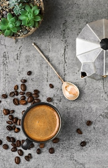 Black cup with espresso coffee, coffee pot and coffee beans on a gray stone table.