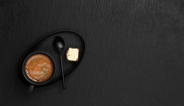 Черная чашка с эспрессо, на блюдце десерт и ложка