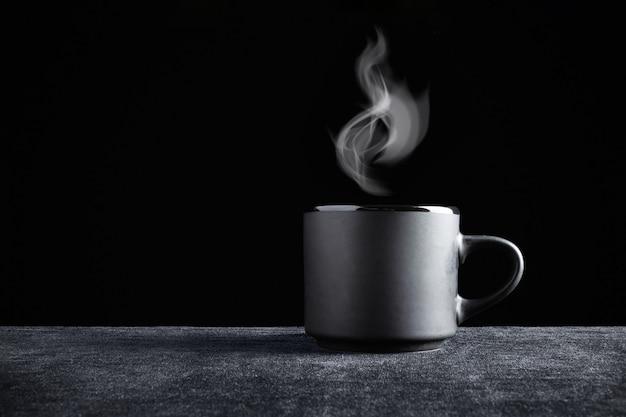 Черная чашка с паром над ней на темной поверхности и черном фоне.