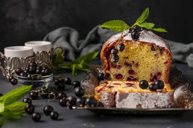 暗い背景、水平方向の写真、クローズアップに対してトレイにある黒スグリのカップケーキ