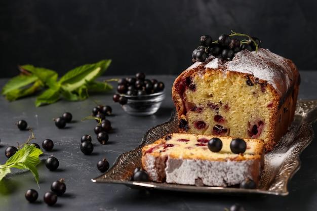 暗い背景のトレイにある黒スグリのカップケーキ