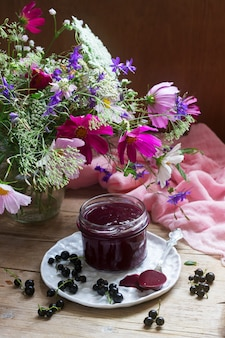 Black currant custard, currants and a bouquet of wild flowers on a wooden background. rustic style.