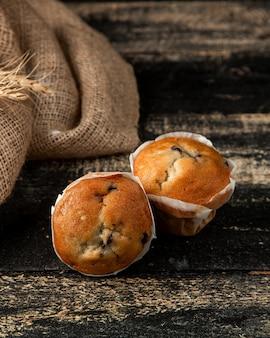 Muffin al ribes nero con ribes nero e grano sul tavolo