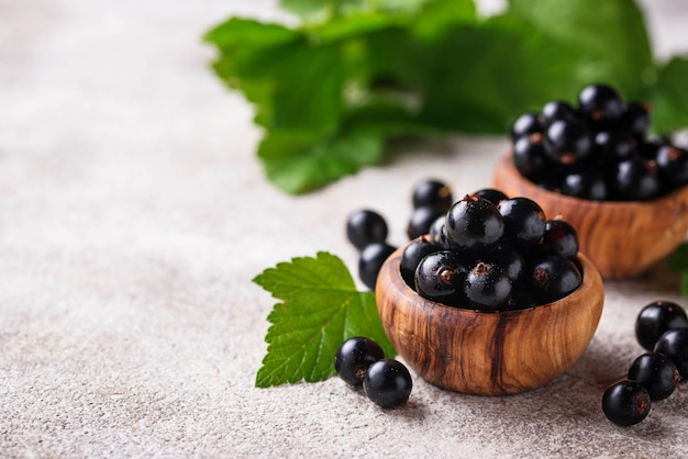 Black currant with leaves in wooden bowls