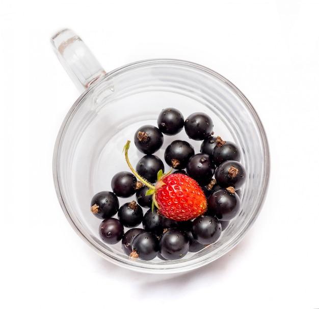 分離された透明なガラスのコップにイチゴと黒スグリ