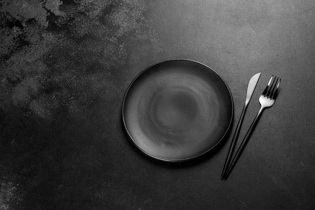 コンクリートの暗いテーブルの上の黒いカトラリー。ダイニングテーブルの準備