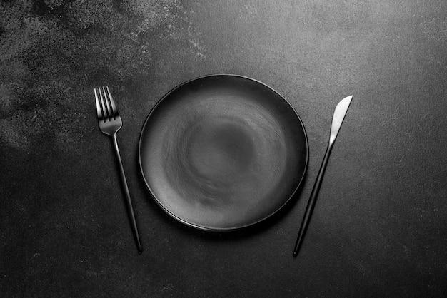 Черные столовые приборы на бетонном темном столе. подготовка обеденного стола