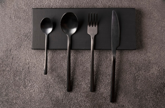 Black cutlery set - fork, spoon, knife, on dark wood . minimalistic still life, stylish dinnerware.