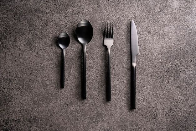 Black cutleryfork spoon knife on a dark background in the center minimalistic flat lay still life
