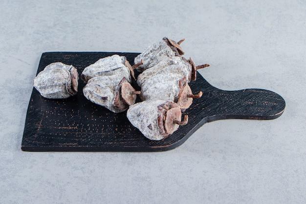 Tagliere nero di frutti di cachi secchi su sfondo di pietra.