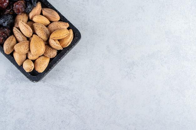 石の背景に乾燥したナツメヤシとナッツでいっぱいの黒いまな板。