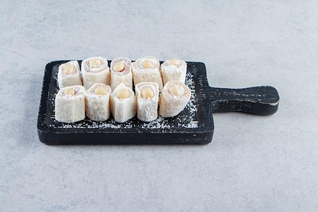Черная разделочная доска вкусных угощений с орехами на каменном фоне.