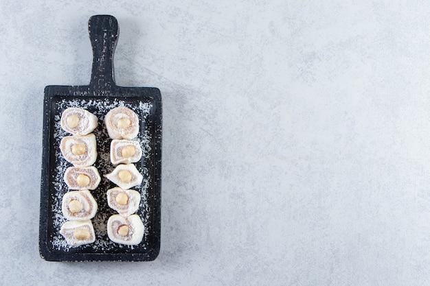 검은색 도마는 돌 배경에 견과류를 넣은 맛있는 음식을 취급합니다.