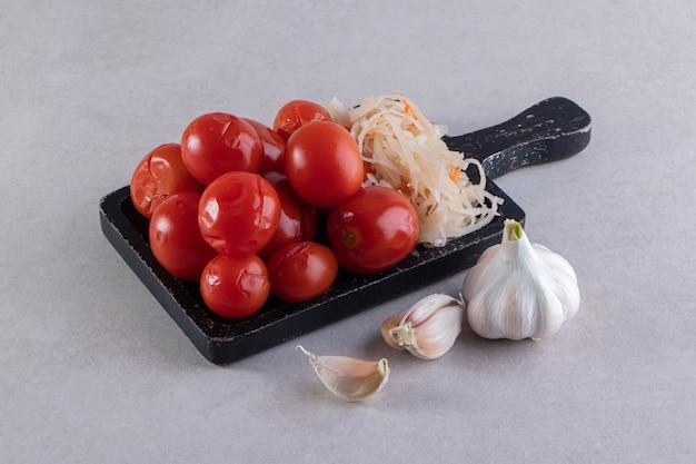 돌에 절인 된 토마토와 양배추의 블랙 커팅 보드.