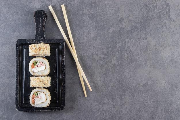 Черная разделочная доска суши-роллов с кунжутом на каменном фоне.