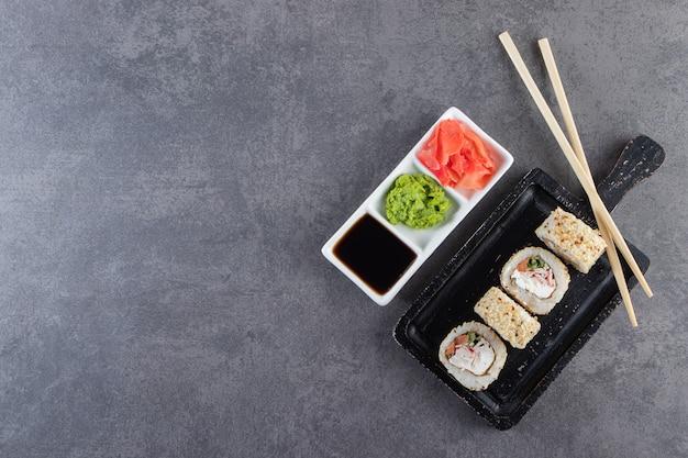 Tagliere nero di rotoli di sushi con semi di sesamo su fondo di pietra.
