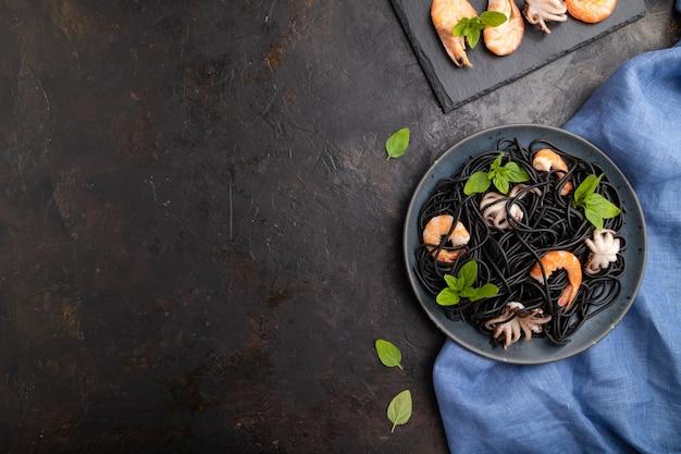 검은 콘크리트 표면과 파란색 직물에 새우 또는 새우와 작은 문어가 들어간 검은 오징어 먹물 파스타