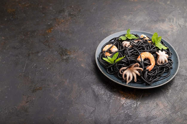 Black cuttlefish ink pasta with shrimps or prawns and small octopuses on black concrete surface