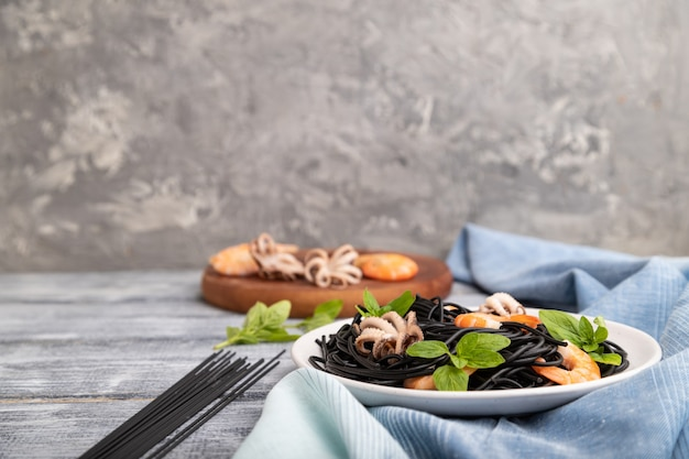 Black cuttlefish ink pasta with shrimps or prawns and small octopuses on gray wooden background and blue textile. side view, copy space, selective focus.