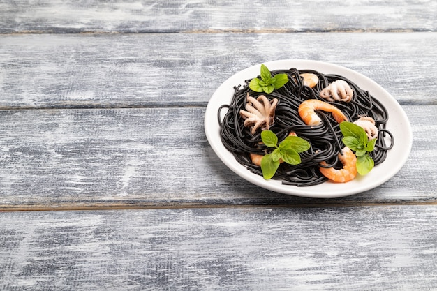Black cuttlefish ink pasta with shrimps or prawns and small octopuses on gray wooden background. side view, copy space.