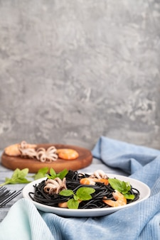 Black cuttlefish ink pasta with shrimps or prawns and small octopuses on gray wooden surface and blue textile