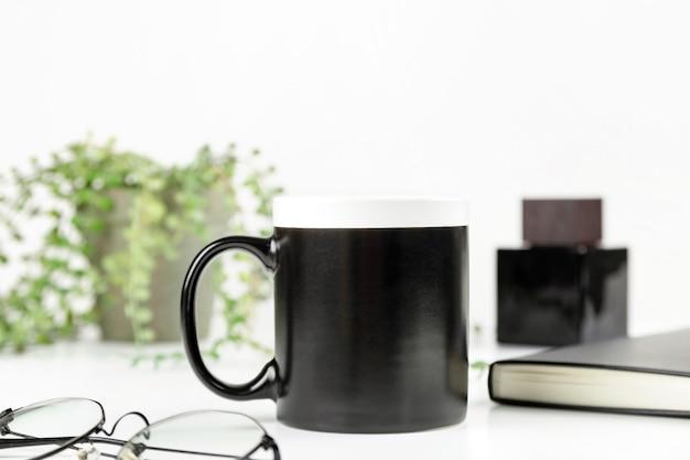 Макет кофейной кружки черного папы на чашке на рабочем месте для дизайна в мужском стиле