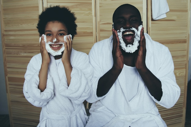 Black dad and son are smeared with shaving foam and smiling.