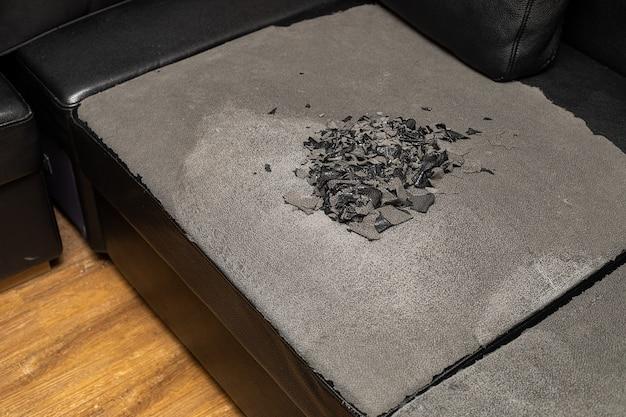 黒の破損したエコレザーソファ。家具の修復修理。救助、ソファの改修。ひびの入った合成皮革の質感。