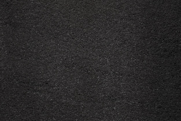 Black dark asphalt with fine grain texture. close-up photo
