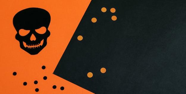 黒オレンジ色のハロウィーンのバナーの背景に黒の装飾的なスカルとエンドウ豆。