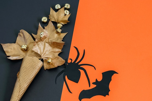 Черный декоративный паук и летучая мышь, золотой вафельный рожок мороженого с листьями на черно-оранжевой бумаге. плоская планировка