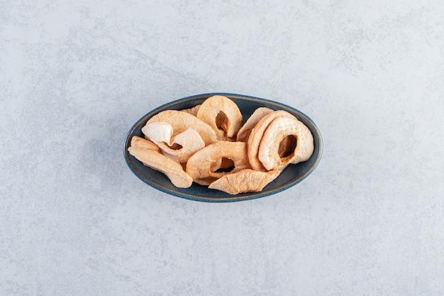 Un piatto fondo nero con mele secche sane su fondo di pietra.